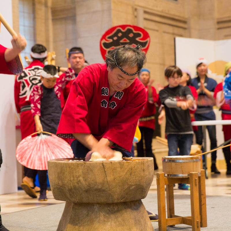 One person wearing a red top and a black headband kneads mochi dough while another person holding a mallet prepares to pound it.