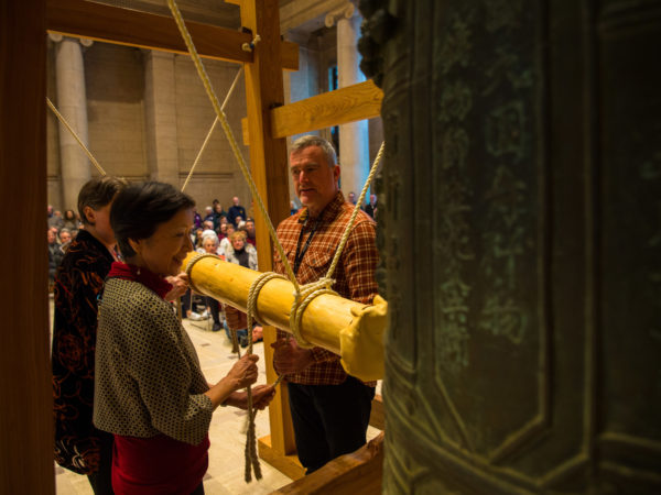 Three people hold wooden beam to ring a large bell