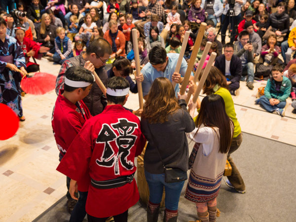 A group of museum visitors pounding mochi with an audience watching