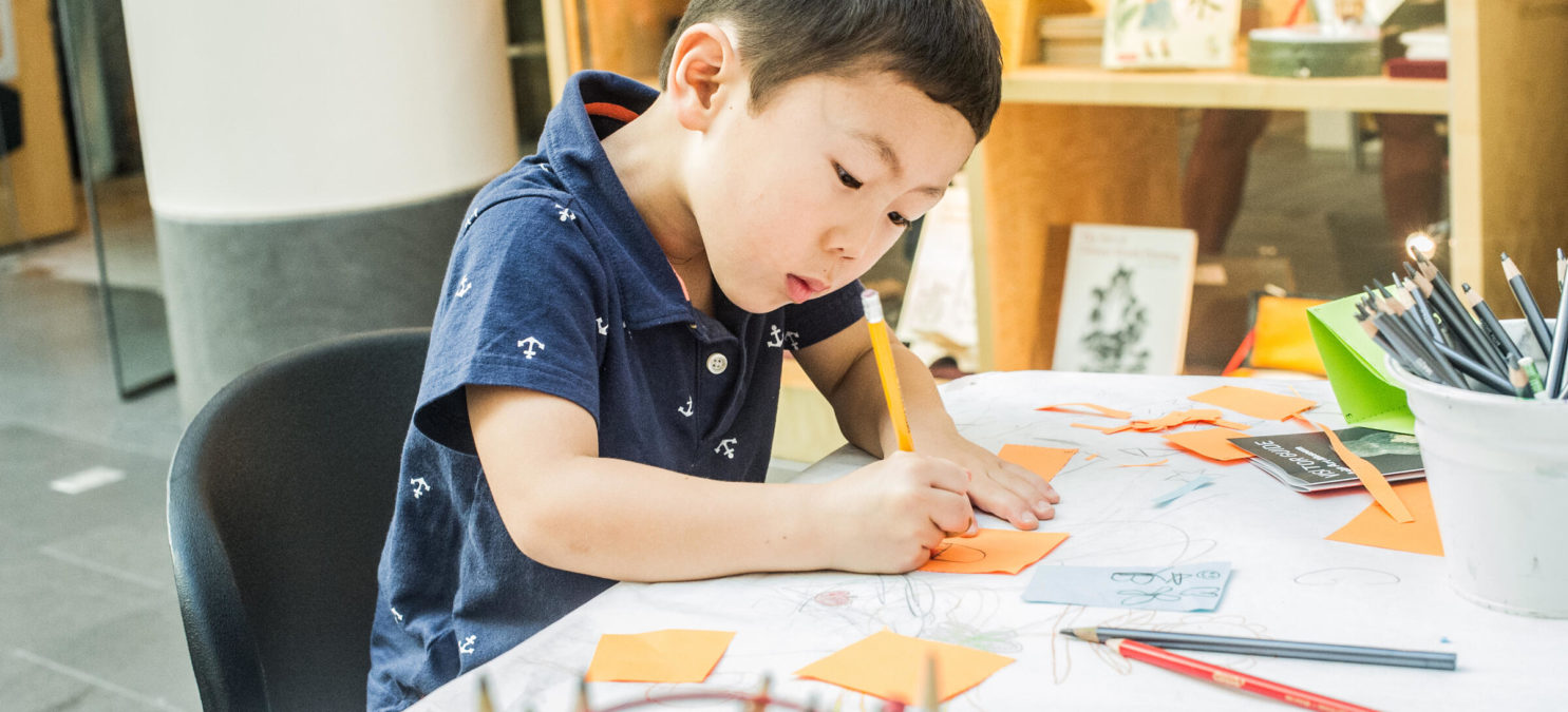 A small child colors on a piece of orange paper.