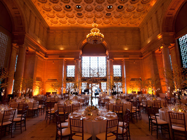 Round dinner tables with elaborate table settings inside a moodily lit ballroom.