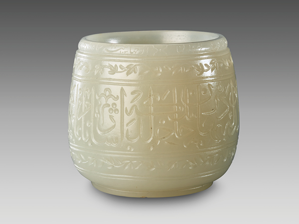 A small, shiny, cream-colored jade cup with Arabic script and flowers carved on the surface.